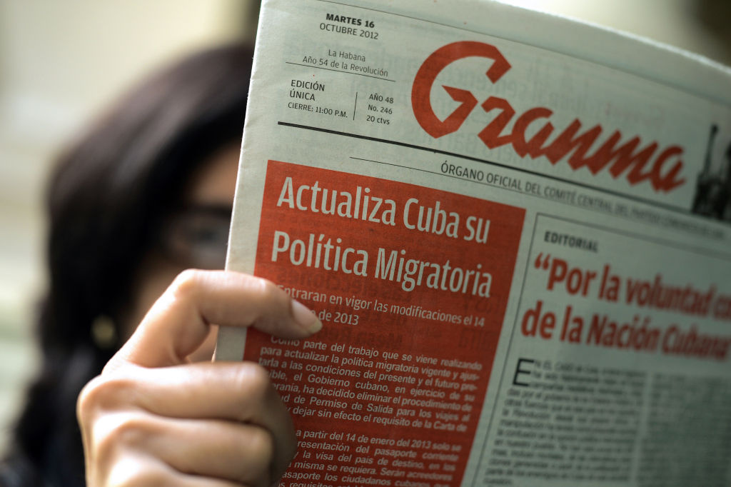 A woman reads a copy of Communist Party's Granma newspaper which informs about a new immigration law, in Havana on October 16, 2012. Cubans will no longer require exit permits for foreign travel from January 14, the government said on Tuesday, the latest in a trickle of reforms enacted on the communist-ruled island. The government has also extended the period citizens are allowed to remain abroad from 11 to 24 months, with the new law set to enter into force 90 days from now, the foreign ministry said in a statement. Cuba has imposed stringent travel restrictions for a half-century but has failed to prevent thousands of its citizens from emigrating illegally each year, sometimes in dangerous sea voyages using rickety boats.