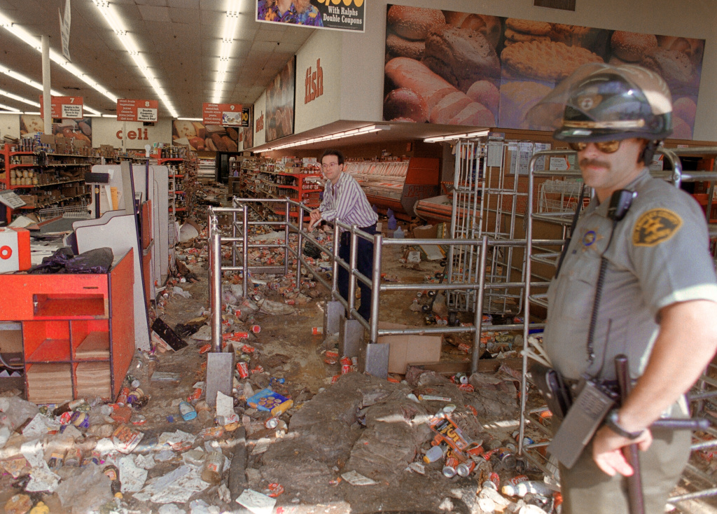 A store owner and a Los Angeles Police Department (LAPD) officer look at the damage caused by looters, 30 April 1992, in Los Angeles. Riots broke out in Los Angeles, 29 April 1992, after a jury acquitted four police officers accused of beating a black youth, Rodney King, in 1991, hours after the verdict was announced.