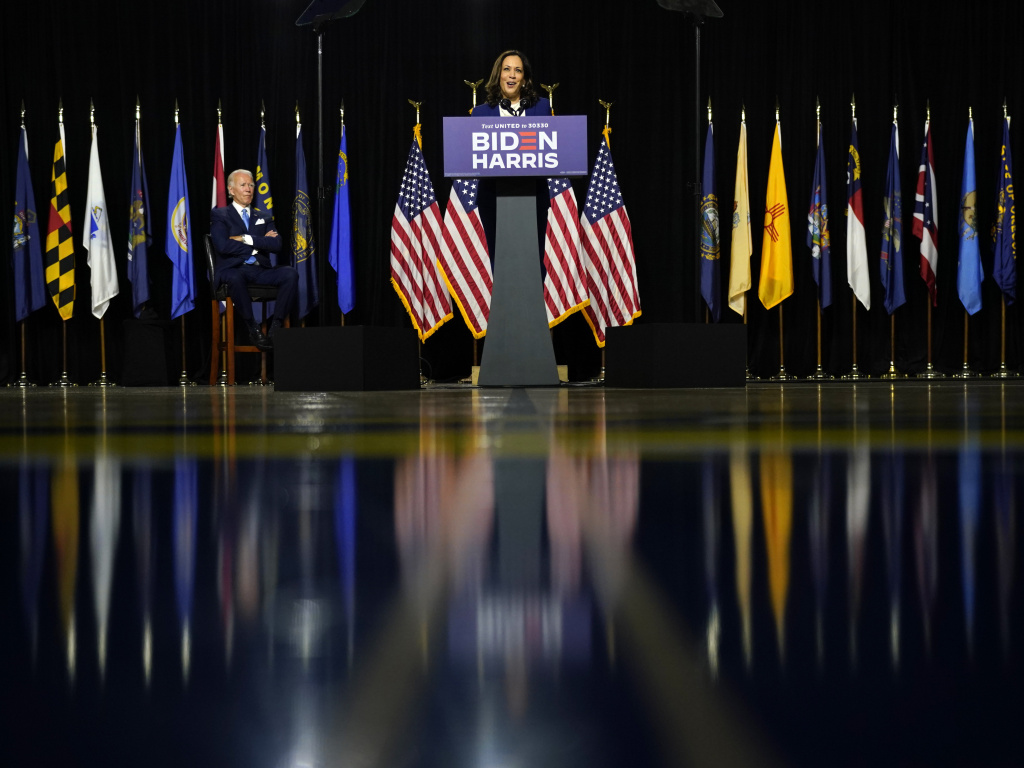 Democratic presidential candidate former Vice President Joe Biden listens as his running mate Sen. Kamala Harris, D-Calif., speaks during a campaign event at Alexis Dupont High School in Wilmington, Del.