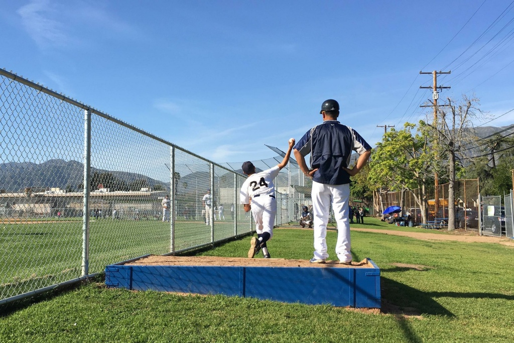 John Muir High School Pitcher Bryan Barrios warms up with coach Robert Galvan.