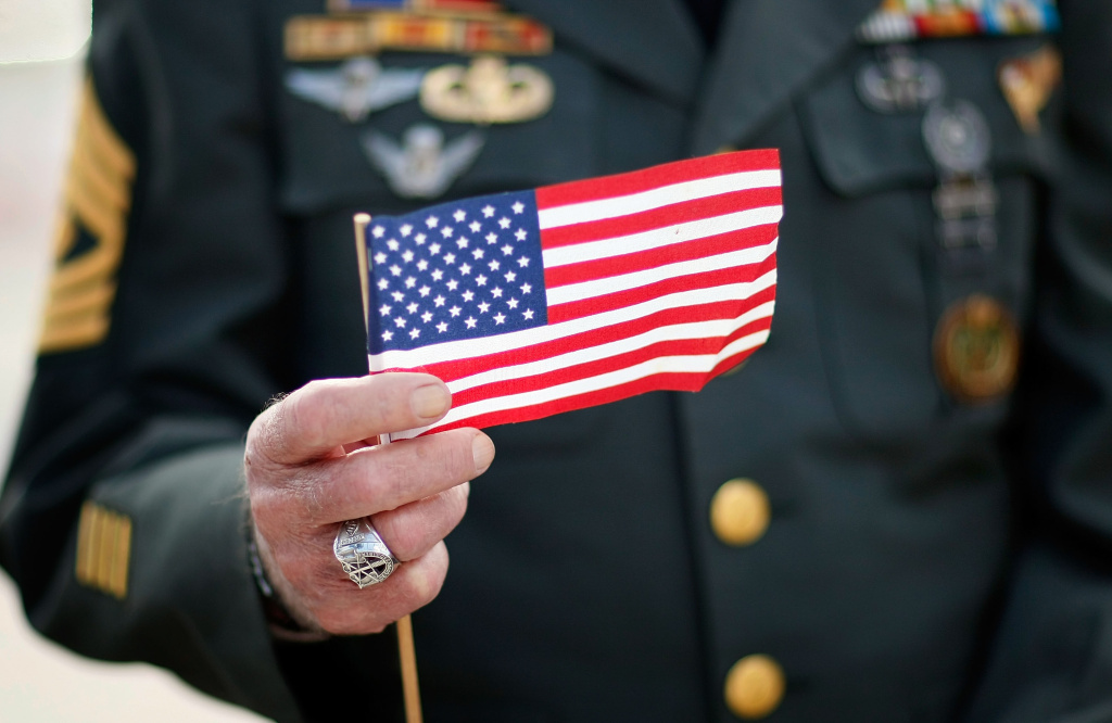 Army veteran Tony Junot holds an American flag during a Veterans Day ceremony November 12, 2007 in Miami Beach, Florida.