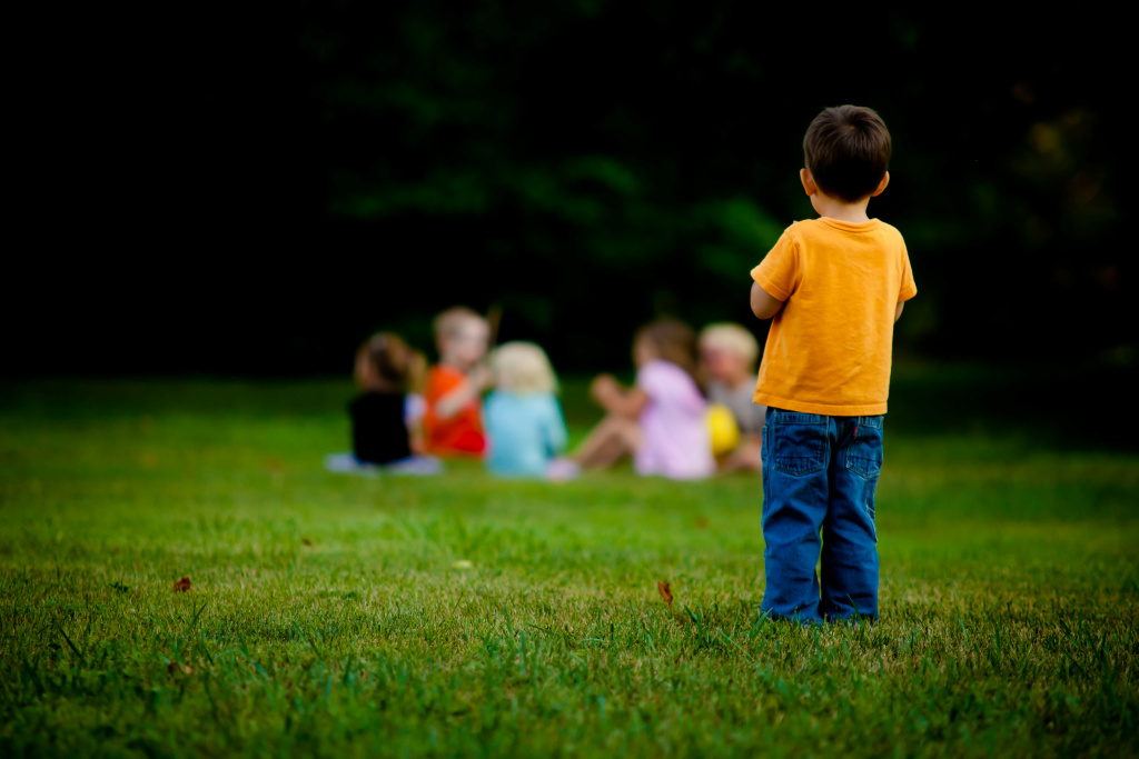 A child stands across a group of other children.