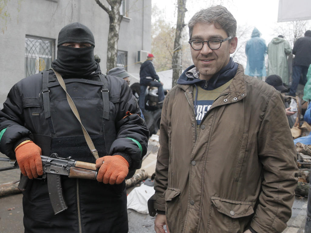 In a photo taken earlier this month, U.S. reporter Simon Ostrovsky, right, stands with a pro-Russian gunman at a seized police station in the eastern Ukraine town of Slovyansk. Ostrovsky has reportedly been seized by the pro-Russian insurgents.