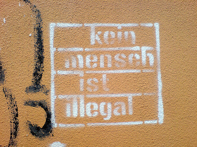 "A sign reading ""no person is illegal"" in German. In the U.S., the debate over whether to use ""illegal immigrant"" to describe a person in the country without permission took a sharp turn this week when The Associated Press announced it was dropping the term from its media stylebook. But people are still at odds over what term to use."