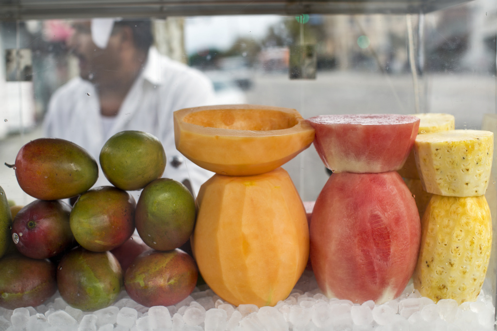 A Highland Park street vendor's cart has mangoes, cantaloupe, watermelon, pineapple, cucumbers and oranges.
