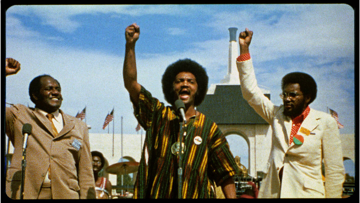 Rev. Jesse Jackson, with Al Bell on the right, leads Wattstax attendees in reciting