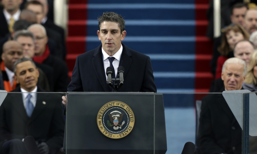 """In this Jan. 21, 2013 file photo, poet Richard Blanco speaks at the U.S. Capitol in Washington during the inauguration for President Barack Obama, left, and Vice President Joe Biden right. Blanco describes writing the inaugural poem in his new book, """"For All of Us, One Today: An Inaugural Poet's Journey.""""  A Cuban-American who grew up in Miami, Blanco says he was he was forced to re-examine his relationship with his adopted country in the weeks leading up to the inauguration."""