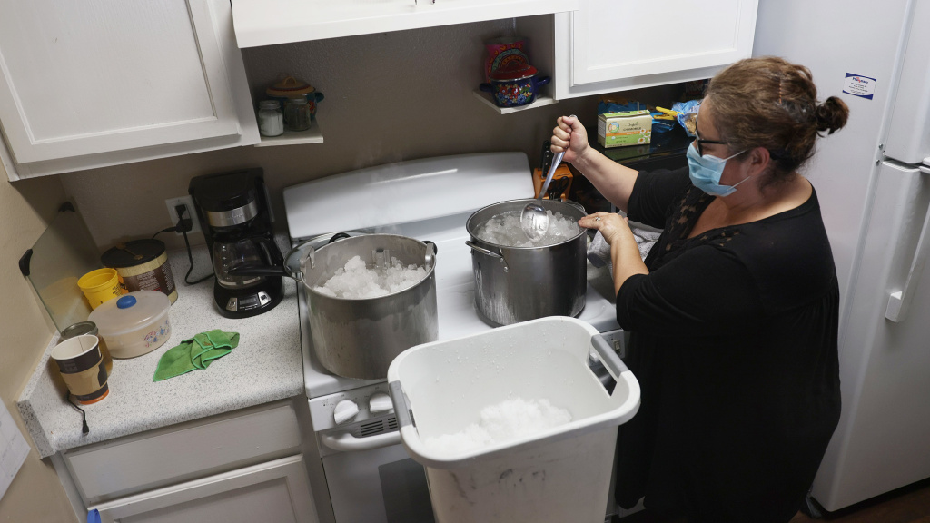 Marie Maybou melts snow on the kitchen stove on Friday in Austin, Texas. She was using the water to flush the toilets in her home after the city water stopped running.