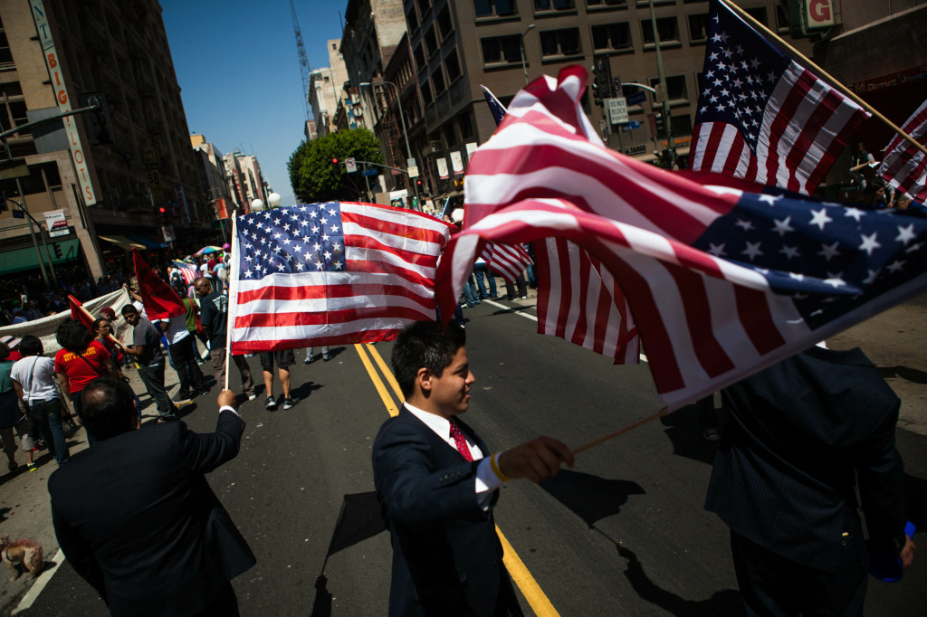 May Day parade goers wave American flags as they make their way down Broadway in Downtown Los Angeles.