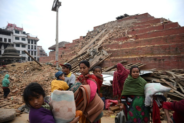 A member of police forces walk down a street covered in debris after buildings collapsed on April 26, 2015 in Bhaktapur, Nepal.