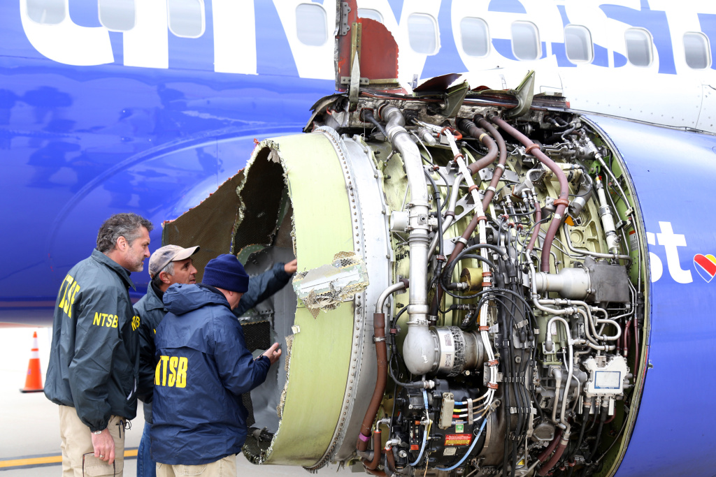 File: In this National Transportation Safety Board handout, NTSB investigators examine damage to the CFM International 56-7B turbofan engine belonging Southwest Airlines Flight 1380 that separated during flight Philadelphia International Airport April 17, 2018 in Philadelphia, Pennsylvania.