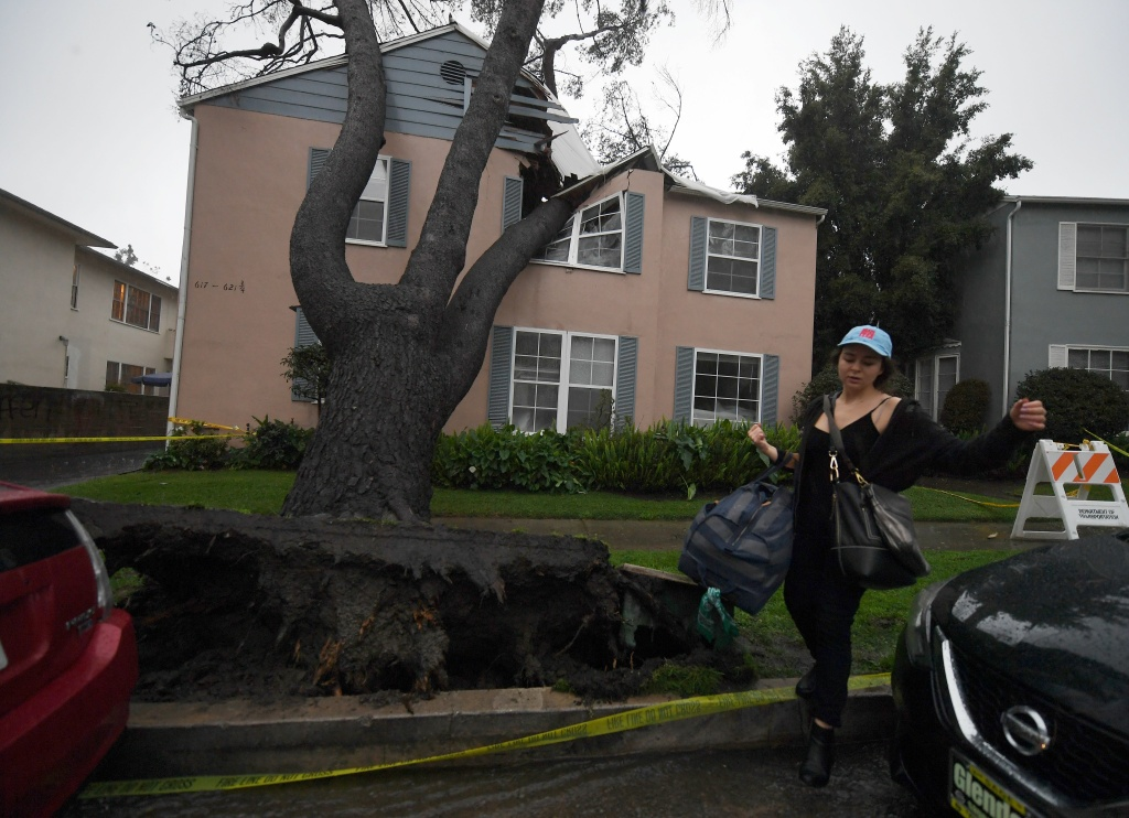 A resident evacuates from her apartment building after a 75-foot-tall tree crashed onto it as the strongest storm in years slams Los Angeles on Feb. 17, 2017.