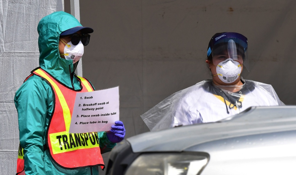 Medical personnel display instructions to motorists for COVID-19 testing in south Los Angeles.