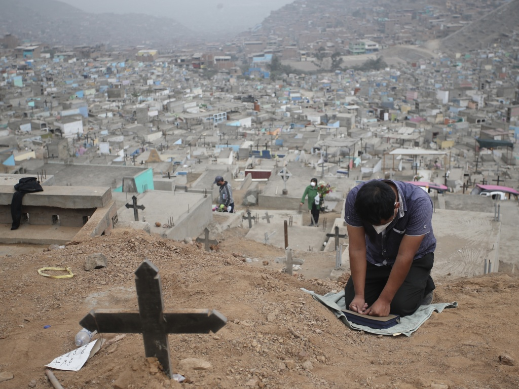 A relative prays at the Mártires 19 de Julio Cemetery on the outskirts of Lima, Peru, on Aug. 20. Peru has one of the highest per capita coronavirus-related death tolls in the world, according to Johns Hopkins University.