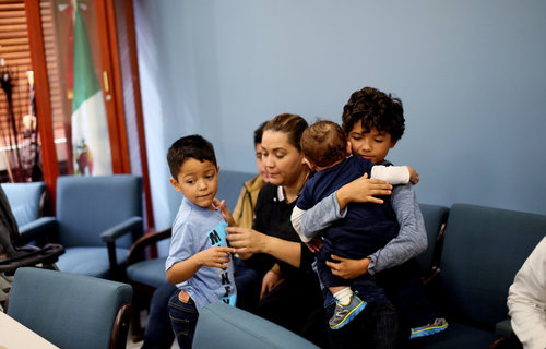 A family waits before a class for new student arrivals to Mexico at the Tijuana Education Department in Tijuana, Mexico.