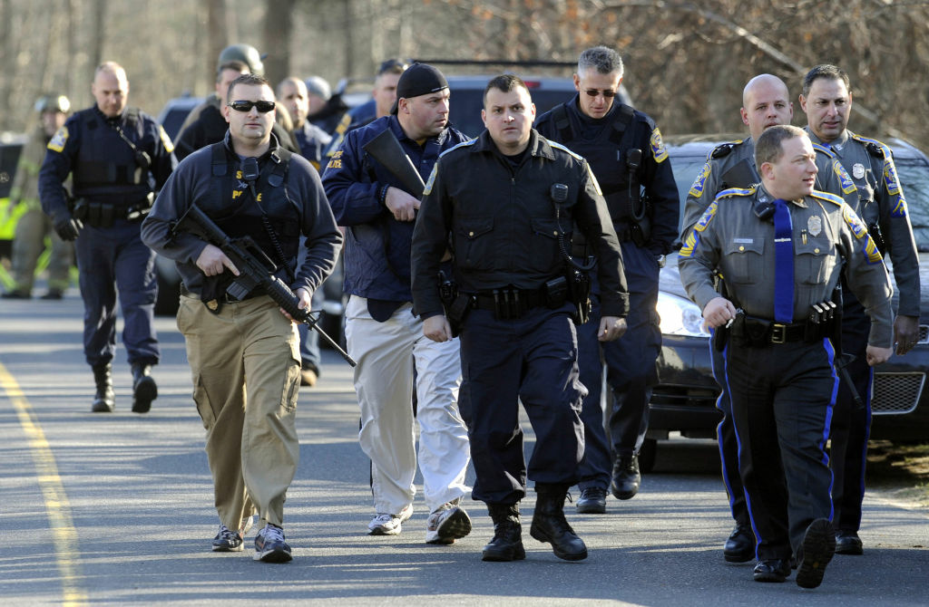 Law enforcement canvass the area following a shooting at the Sandy Hook Elementary School in Newtown, Conn., about 60 miles (96 kilometers) northeast of New York City, Friday, Dec. 14, 2012. An official with knowledge of Friday's shooting said 27 people were dead, including 18 children.