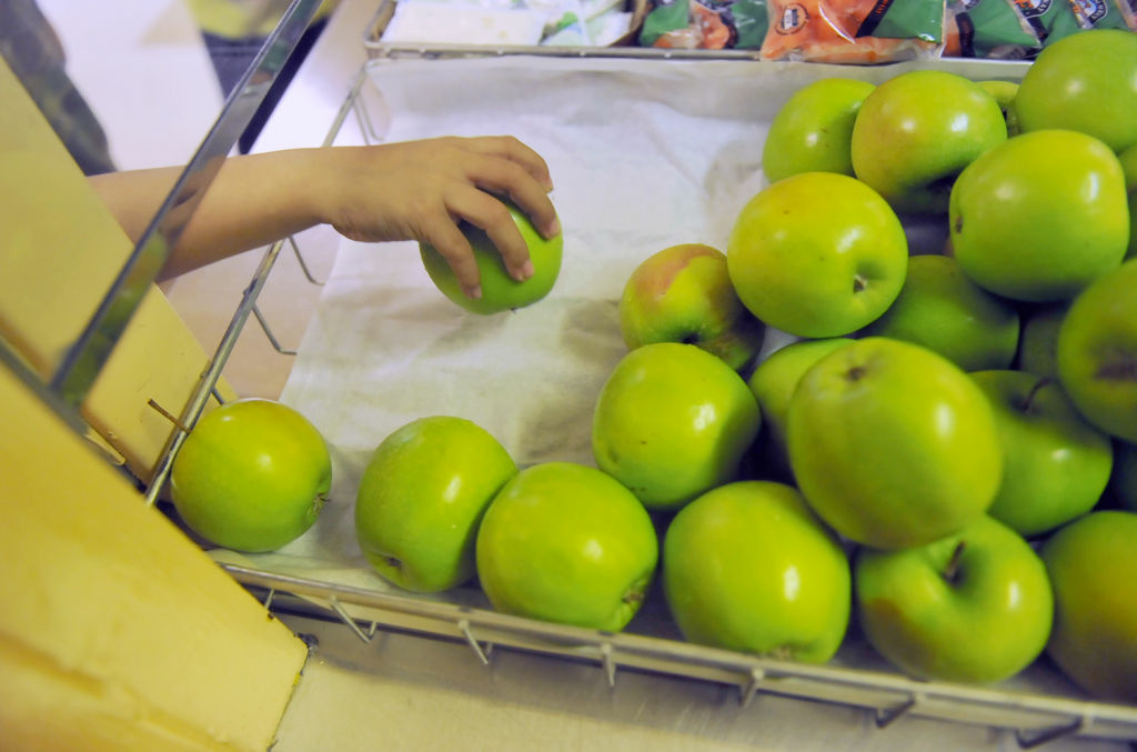 A student grabs an apple during lunch period at Brockton Avenue Elementary School in Los Angeles. Beginning this week (July 1), schools around the country are required to serve fruits and vegetables every day and boost whole-grain products. Credit: Richard Hartog for California Watch