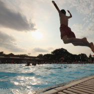 A boy jumps as people bathe on opening day of the newly renovated McCarren Park Pool on June 28, 2012 in the Brooklyn borough of New York City.