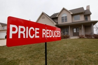 A sign sits in the front yard of a home being offered for sale in Pleasant Prairie, Wisconsin. The Case-Shiller index shows housing prices dropped in March to their lowest point since the housing bubble burst in 2006.