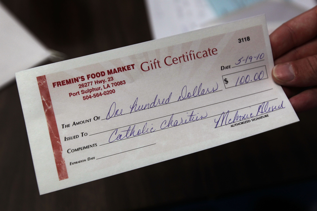 A gift certificate for a local grocery store is written out for fishermen and their families at an aid station on May 20, 2010 in Port Sulphur, Louisiana. The Catholic Charities Archdiocese of New Orleans distributed the vouchers to families affected by the BP oil spill.