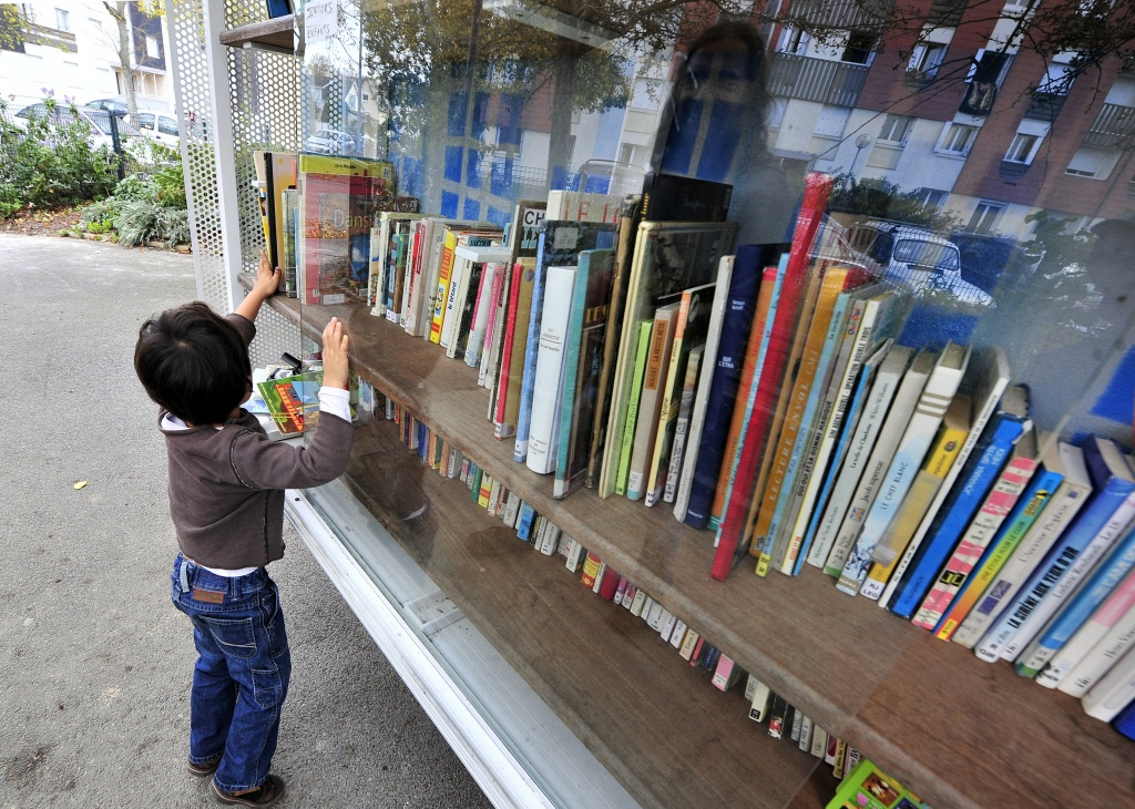 A child looks at books in a library in a street of the Bel Air district in the city of Rennes, France, on October 22, 2014.