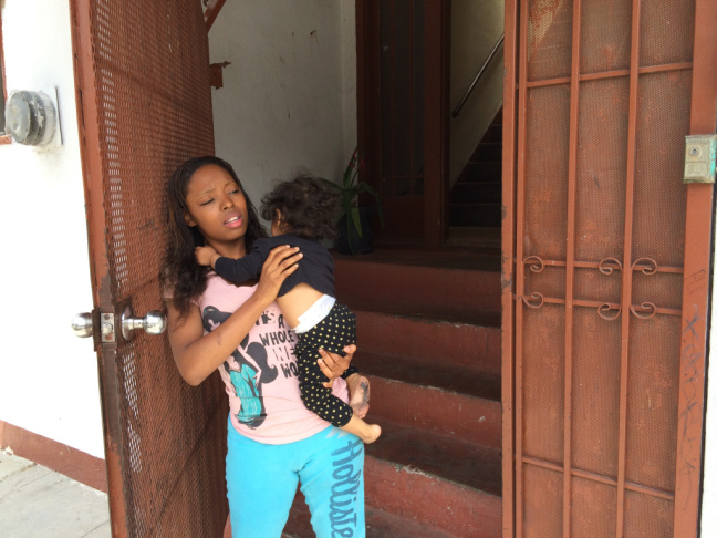 19 year-old Shantoya Byrd in front of her Los Angeles apartment complex where she and her daughter, Anmarie Paz, live. They have just waved goodbye to CHLA therapist, Lorena Samora, who visits weekly to provide coaching and assistance to deal with Anmarie's separation anxiety.