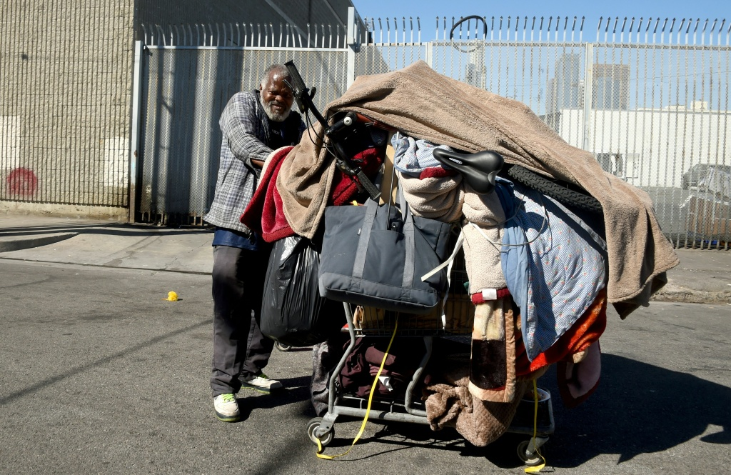 A homeless man pushes his cart of belongings along a street in Los Angeles, California on February 9, 2016.