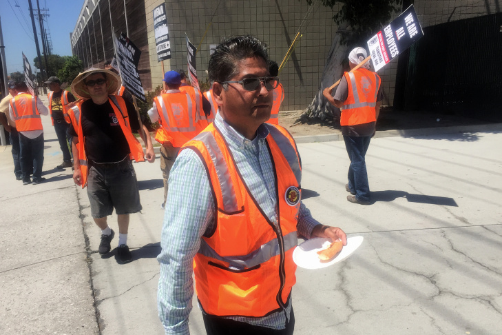 Daniel Linares, 58, eats lunch on the picket line outside
