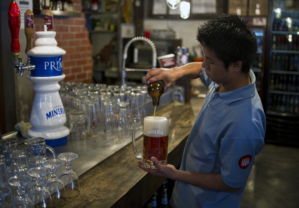 A barman serves Mexican craft beer in a bar in Mexico City, on July 20, 2012. Producers of handcrafted beer make their way in Mexico following the emergence of new breweries in crowded neighborhoods of the capital and as large emporiums producing traditional brands such as Corona stopped being Mexican.