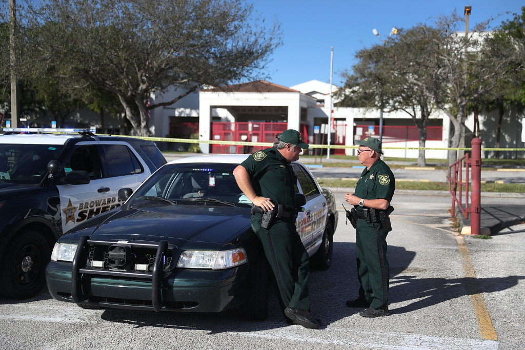 Broward County Sheriff officers, Brad Griesinger and Jamie Rubenstein (L-R) stand guard at the entrance to Marjory Stoneman Douglas High School on February 18, 2018 in Parkland, Florida.