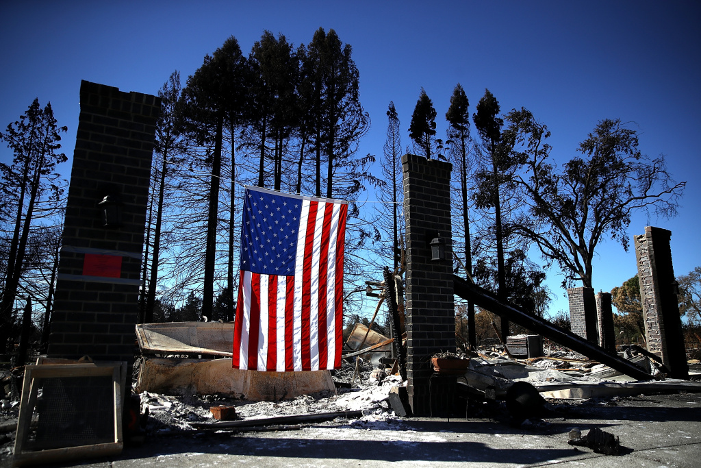 SANTA ROSA, CA - OCTOBER 23:  An American flag hangs in front of a home in the Coffey Park neighborhood that was destroyed by the Tubbs Fire on October 23, 2017 in Santa Rosa, California. Residents are returning to their homes after a fast moving and deadly widlfire destroyed 8,400 structures and claimed the lives of at least 42 people. (Photo by Justin Sullivan/Getty Images)