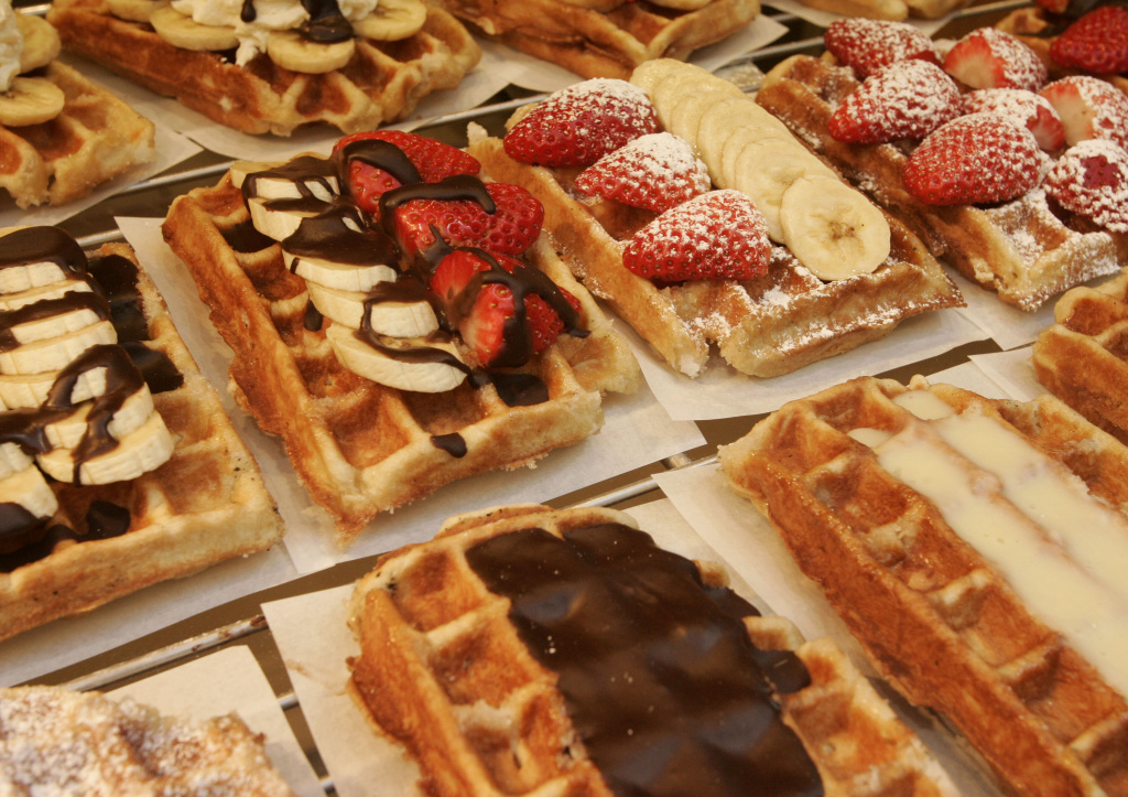 A photo shows decorated Belgian waffles sitting on cooling racks.