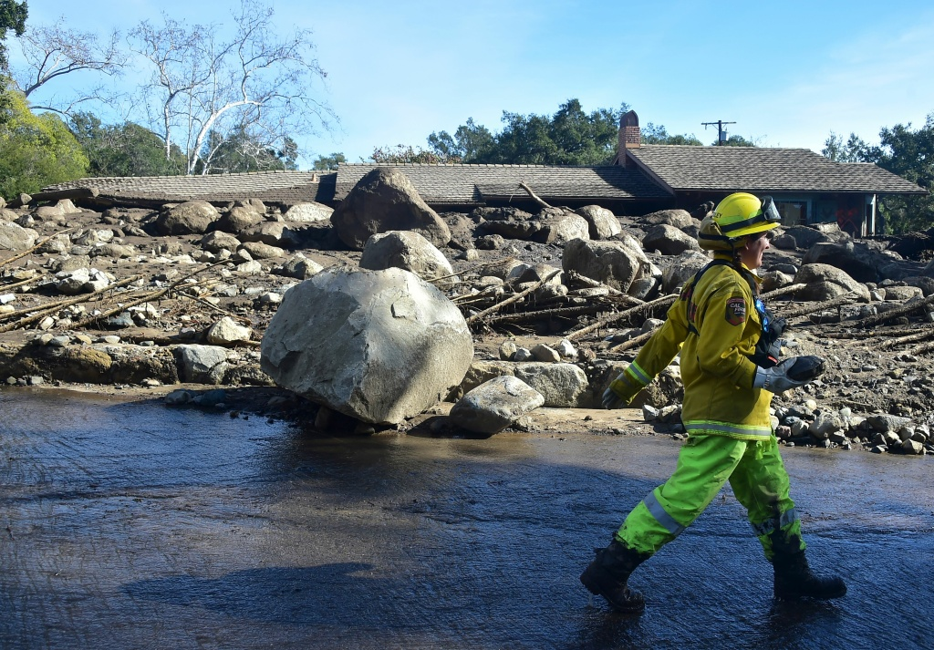 A rescue worker walks past debris near a property in Montecito, California January 12, 2018.