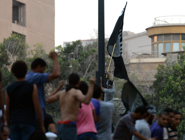 Egyptian protesters raise inside the US embassy a black flag inscribed with the Muslim profession of belief: 'There is no God but God and Mohammed is the prophet of God' during a protest against a film deemed offensive to Islam in Cairo on September 11, 2012.