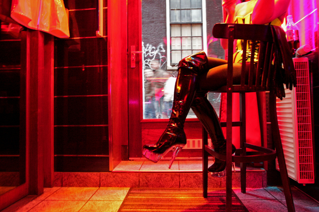 File: A German prostitute, called Eve, waits for clients behind her window in the red light district of Amsterdam on December 8, 2008.