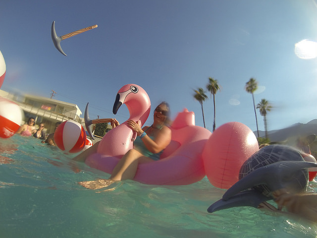 A woman rides a pink swan floatie in the pool of the Ace Hotel in Palm Springs.
