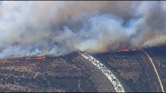 In this frame from video provided by NBC4, smoke rises from vehicles as a fast-moving wildfire swept across a freeway Friday, July 17, 2015, near Hesperia, Calif. The fire swept by desert winds burned on both sides of Interstate 15, the main connector between Southern California and Las Vegas that was crowded with vehicles.