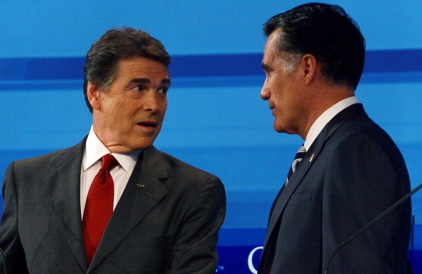 Texas Gov. Rick Perry and former Massachusetts Gov. Mitt Romney speak during a break in the Fox News debate in Orlando on September 22, 2011