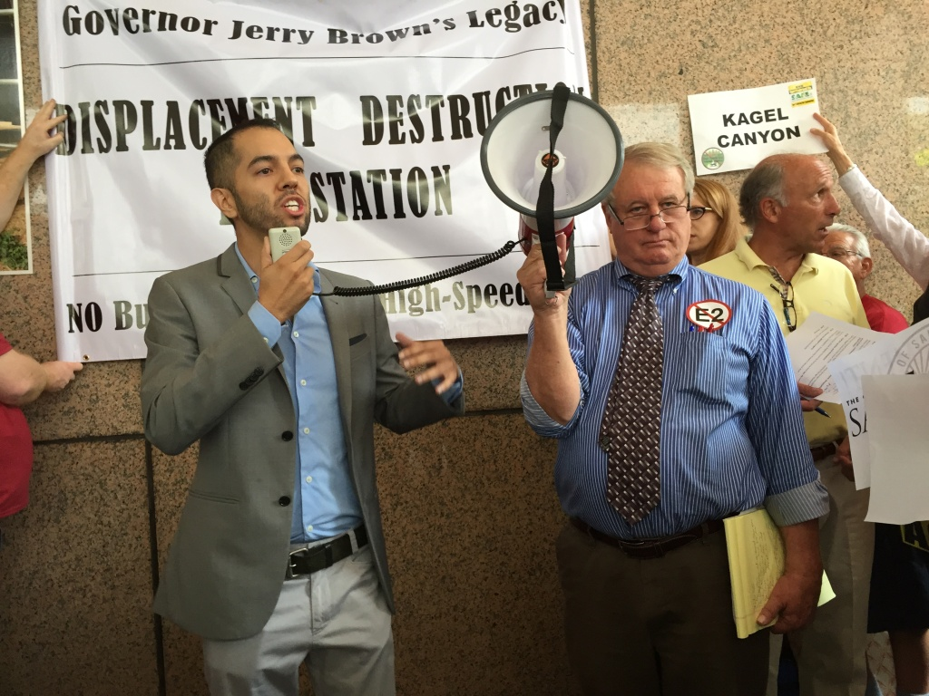 San Fernando Mayor Joel Fajardo and activist Bill Eick protest in front of the California High Speed Rail Authority meeting June 9, 2015.