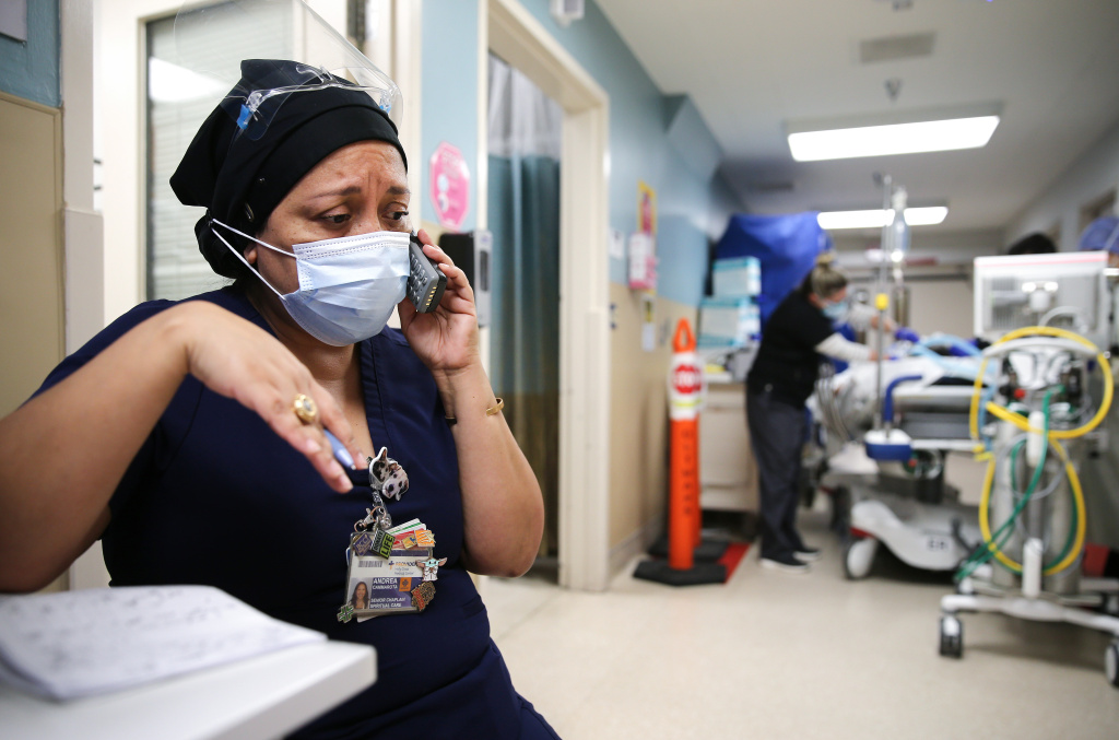 Senior chaplain Andrea Cammarota speaks with a patient's family  in the Emergency Department at Providence Holy Cross Medical Center in the Mission Hills neighborhood on February 17, 2021 in Los Angeles, California.
