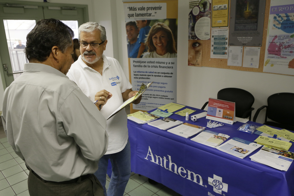 In this Oct. 1, 2013, file photo, Alberto Pizon, right, a representative of Anthem BlueCross BlueShield Latino Health Access group provides free information to Paulino Zarate, 65, left, on the new health options available during a health fair promoted at the Binational Health Week event held at the Mexican Consulate in Los Angeles. A new Field Poll released Wednesday, August 15, found 58 percent of registered voters in California support extending Medi-Cal services to immigrants in the country illegally, who are not currently eligible for coverage under the Affordable Care Act.