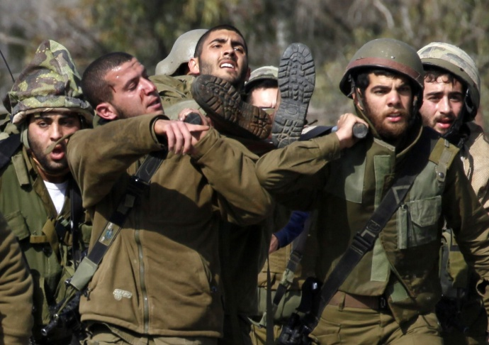 Israeli soldiers carry their injured comrade in the divided village of Ghajar after an anti-tank missile hit an army vehicle in an occupied area on the border with Lebanon on January 28, 2015. At least four Israelis were wounded, sparking a cross-border firefight.