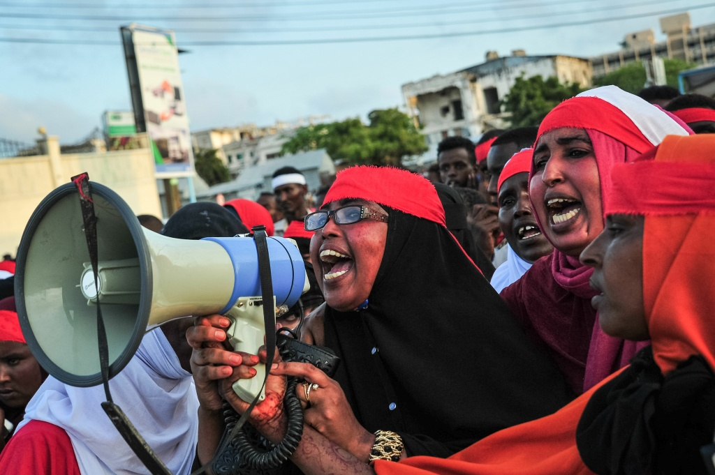 People chant slogans as they protest after a truck bomb exploded outside of the Safari Hotel in Mogadishu on October 15, 2017.