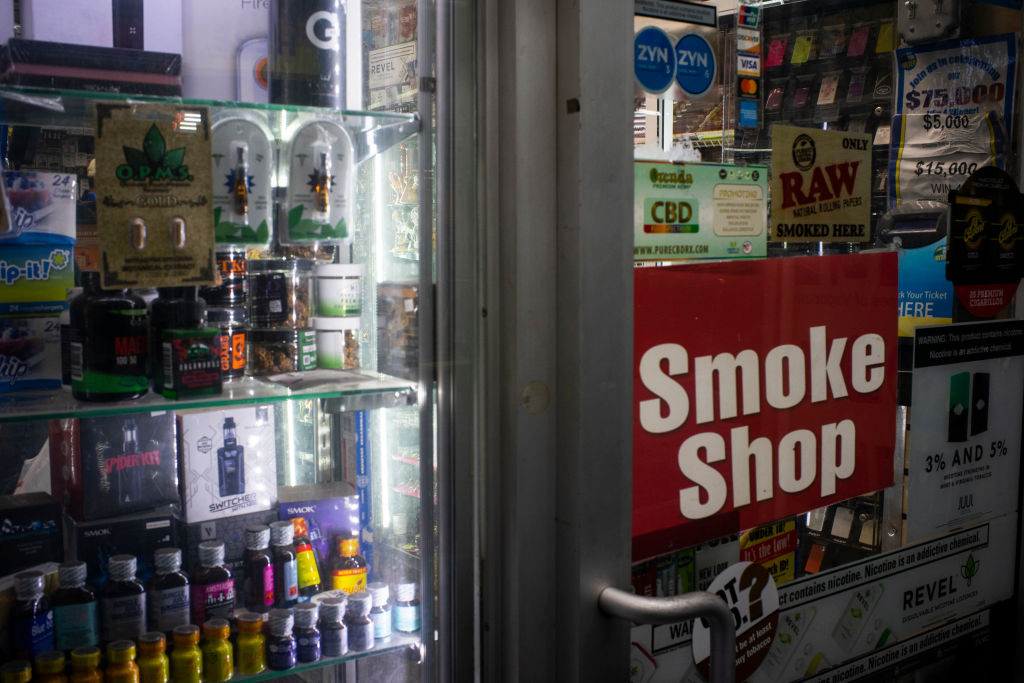 Flavored e-cigarettes are displayed in a store window.