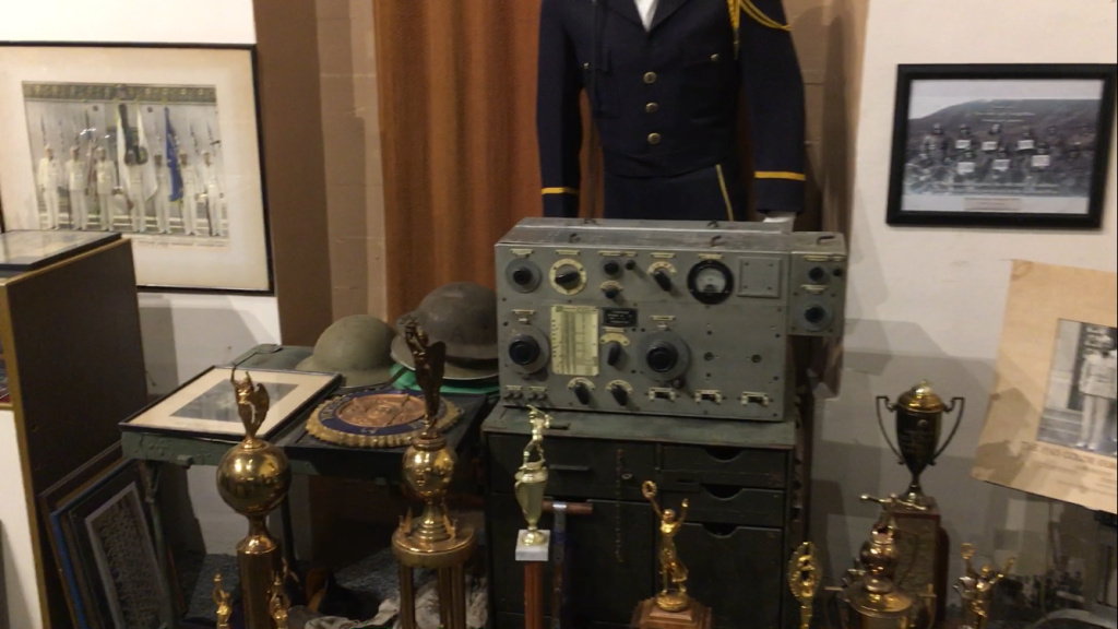 A Japanese radio captured during WWII, surrounded by old trophies.