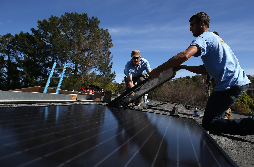 SolarCraft workers Joel Overly (L) and Craig Powell (R) install a solar panel on the roof of a home on February 26, 2015 in San Rafael, California.
