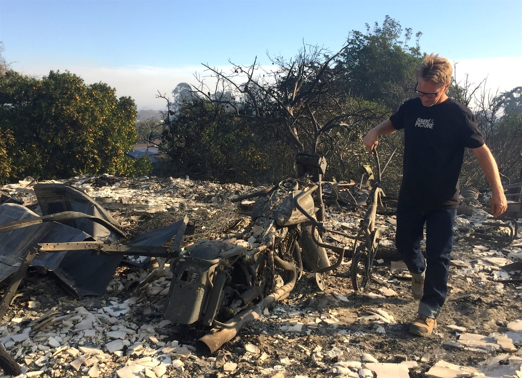 Chris Cairns carries his grandson's bicycle out of the ashes of his garage on Foothill Road in Ventura.