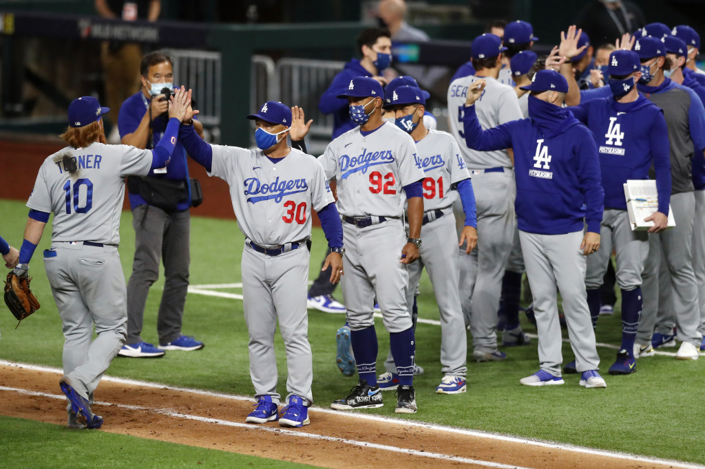 Manager Dave Roberts of the Los Angeles Dodgers celebrates with players after defeating the San Diego Padres in Game Three of the National League Division Series at Globe Life Field.