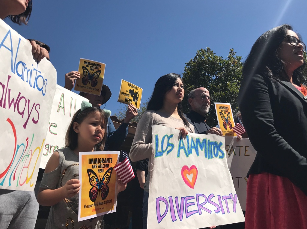 Residents from Los Alamitos show support for immigrants during a news conference announcing a lawsuit against the city for its ordinance exempting the city from the California Values Act, also known as the state sanctuary law.