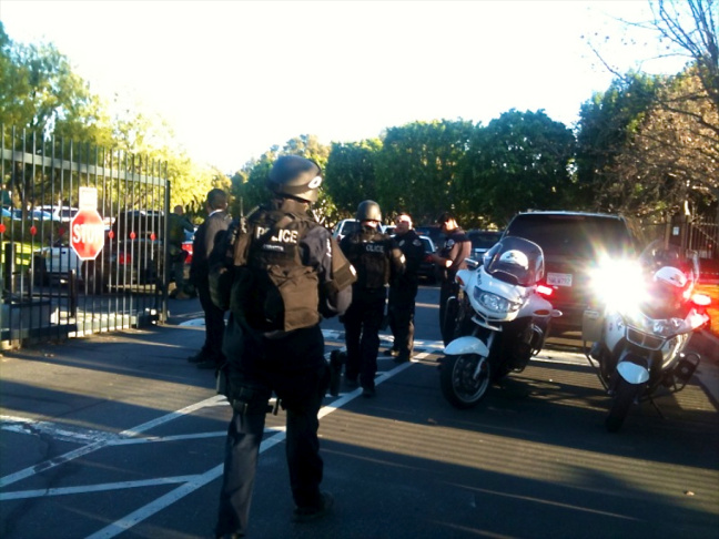 Police officers block the entrance of the office building that houses offices of Southern California Edison after a man armed with a rifle shot two people, then shot himself in Irwindale, Calif., Friday, Dec. 16, 2011.